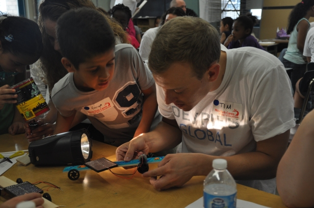 A lot of New York Cares projects are possible because of corporate volunteers. Here, volunteers from Devries Global helped students make solar powered cars.